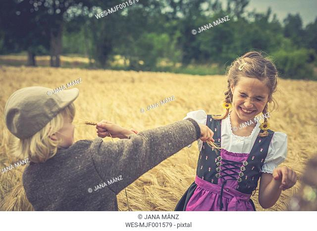 Germany, Saxony, two children playing in a grain field