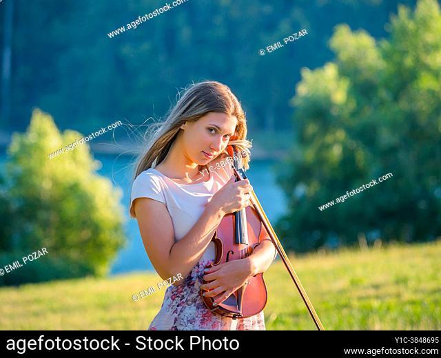 Idyllic teenager girl violin player in nature looking at camera