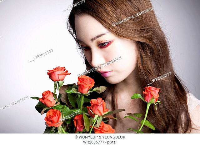 Portrait of young Korean woman in red eye liner with red roses looking down