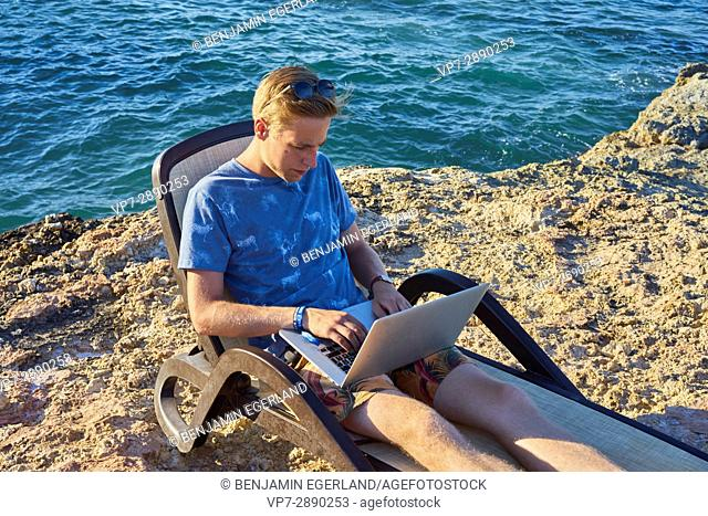 young man using laptop computer in sunbed next to sea in holiday location Hersonissos, Crete, Greece