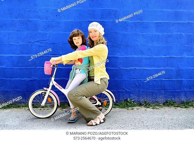 7 years old girl on bicycle and her mother front a blue wall in Caños de Meca, Cádiz, Andalucia, Spain