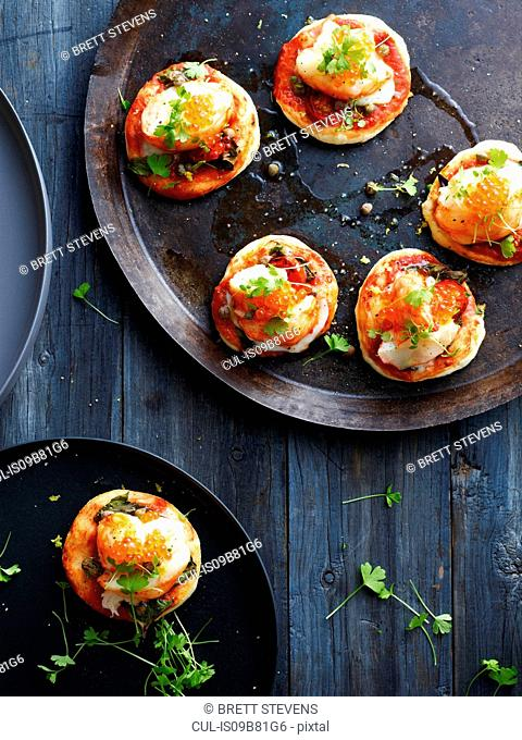 Mini lobster pizzas on serving plate, overhead view