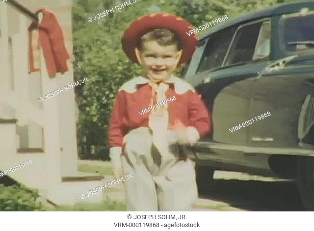 3-year old smiling boy in red cowboy outfit walks down stairs and by antique car, then smiles while walking into the camera