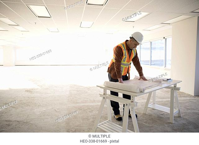 Contractor reviewing blueprints in empty, unfinished open plan office