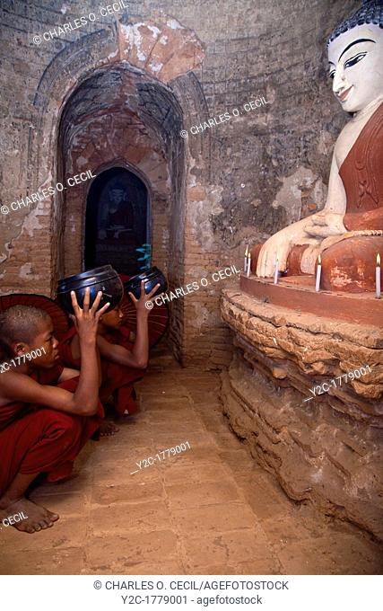 Myanmar, Burma  Bagan  Two Young Novice Monks Praying in front of Buddha Statue