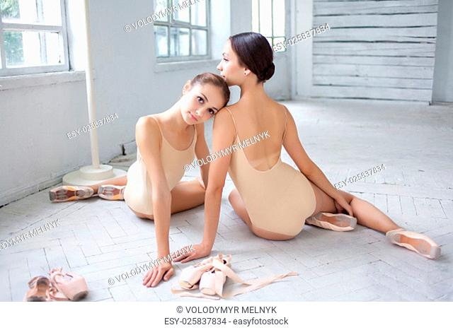 The two classic ballet dancers sitting and posing on white wooden floor