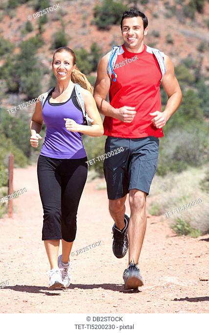 USA, Arizona, Sedona, Young couple running in desert