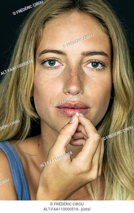 Young woman preparing to take pill