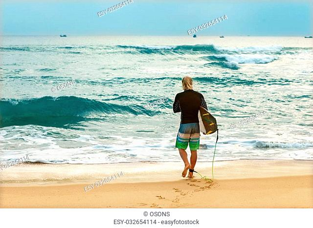 Surfer at the sea is standing with a surf board bright color