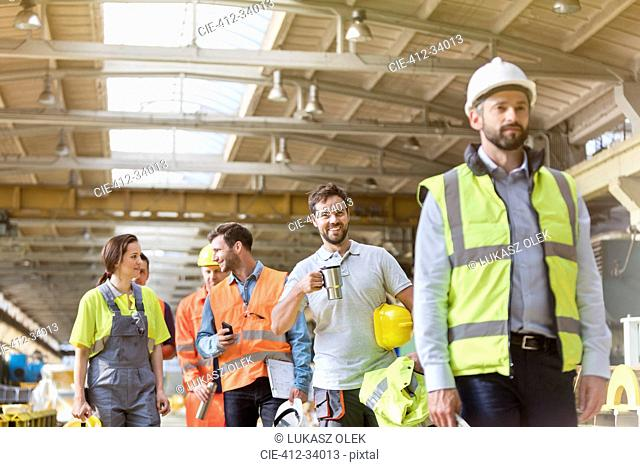 Steel workers talking and walking on coffee break in factory