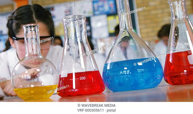 Schoolgirl observing chemicals in laboratory