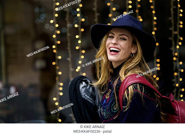 Portrait of laughing young woman wearing blue hat