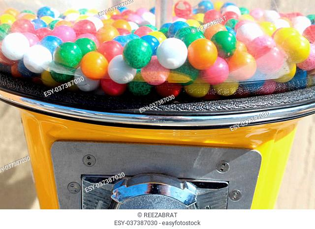 Bright yellow bubble gum machine with many colorful balls of flavorful gum