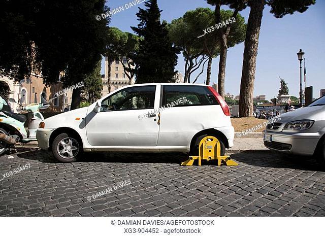 Yellow wheel clamp on white Fiat car, Rome, Italy