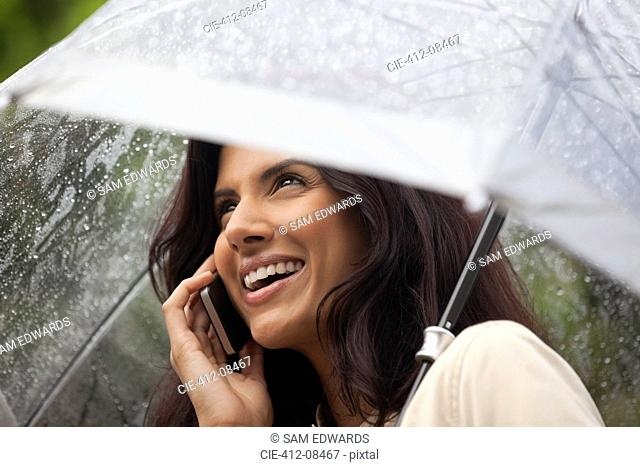 Happy woman talking on cell phone under umbrella in rain