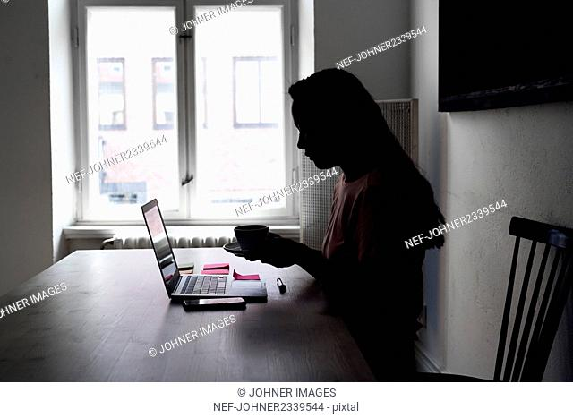 Woman having coffee in front of laptop
