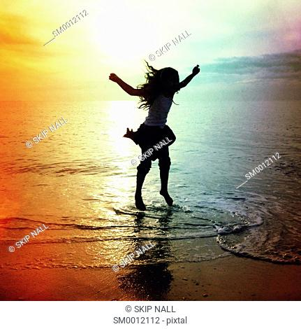 Little girl dancing in the water at the beach