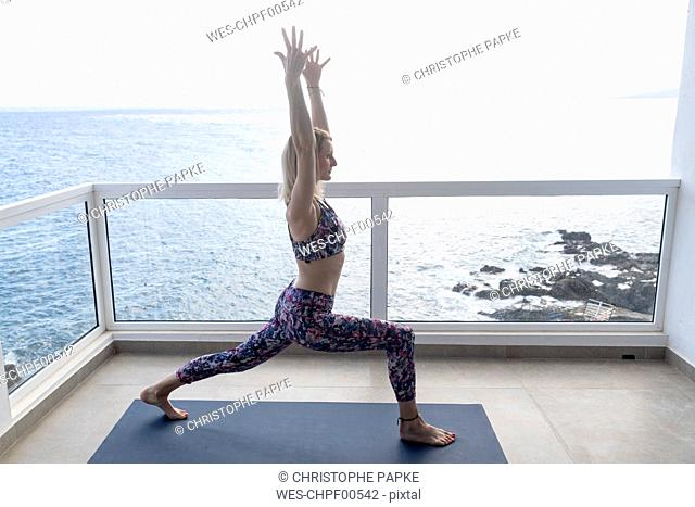 Woman practicing yoga on balcony, Position 'High Lunge', Tenerife, Spain