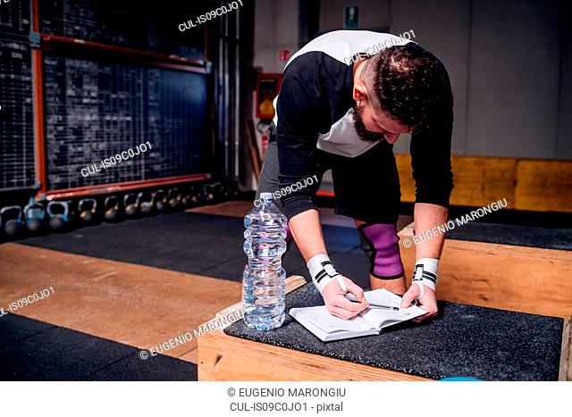 Young man reading checklist on notebook in gym