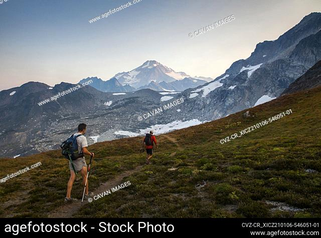 Two hikers climb towards the summit of Glaicer Peak in Washington
