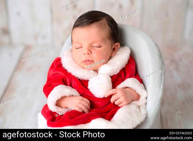 Portrait of one week old newborn baby girl sleeping in a chair and wearing a red and white Mrs. Claus dress