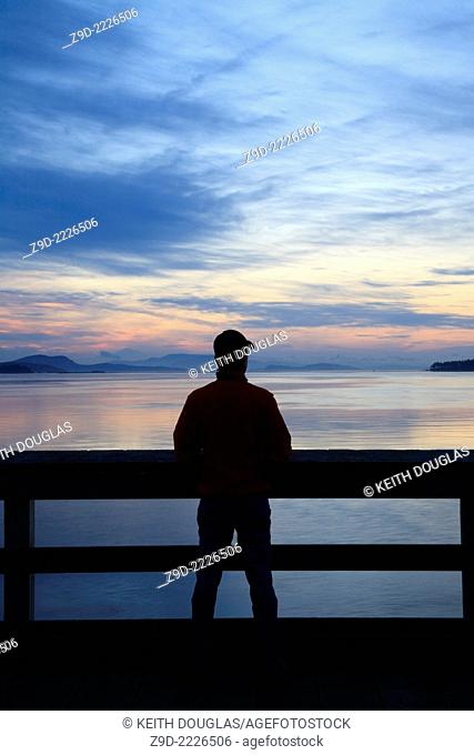 Person on fishing pier at dawn, Sidney, British Columbia