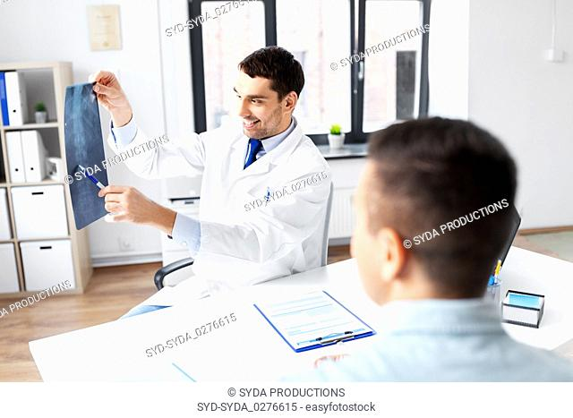 doctor showing x-ray to patient at hospital