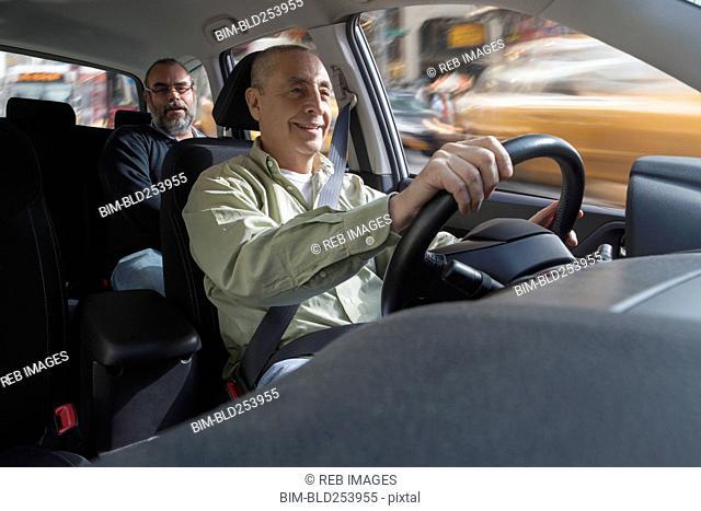 Smiling Hispanic man driving car with passenger