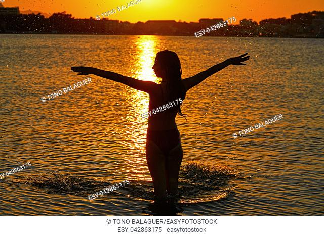 Girl silhouette at beach sunset open arms standing