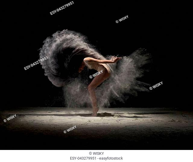 Contemporary art - full length shot of young graceful dancer at dark studio moving in cloud of powder or dust