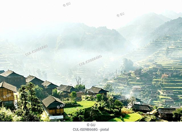 Misty mountain valley landscape and Xijiang village, Guizhou, China