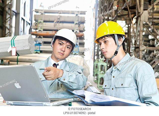 Warehouse Workers Using Laptop