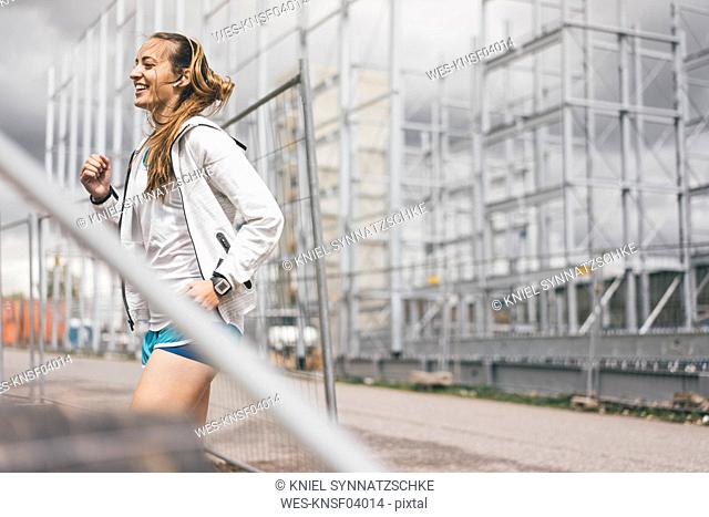 Happy sportive young woman standing at hoarding