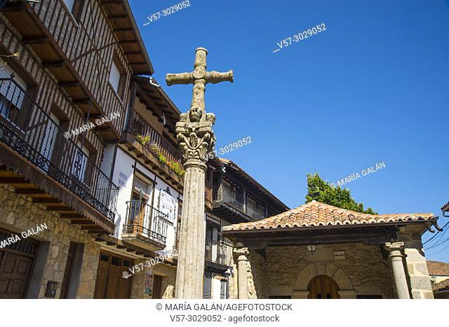 Stone cross and facades of houses. Mogarraz, Sierra de Francia, Salamanca province, Castilla Leon, Spain