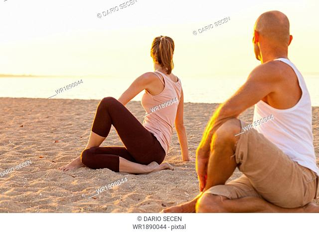 People practising yoga on beach, rear view