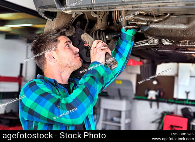 Handsome car mechanic checking suspension system of a lifted car at repair service station