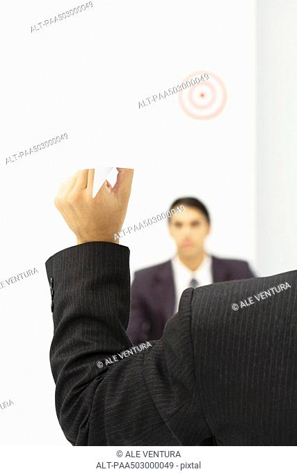 Man holding paper airplane, aiming at target over colleague's head, cropped view