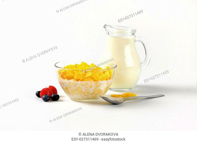 bowl of corn flakes and jug of milk on off-white background with shadows