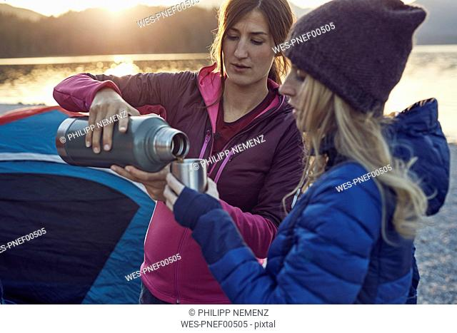 Two women with hot drink camping at lakeshore