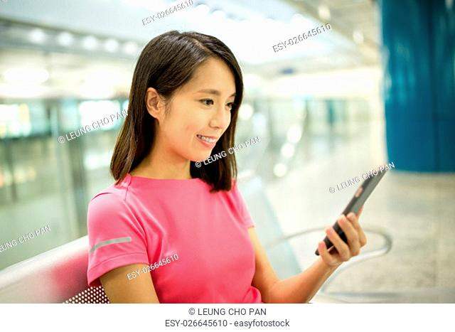 Woman using cellphone in train station