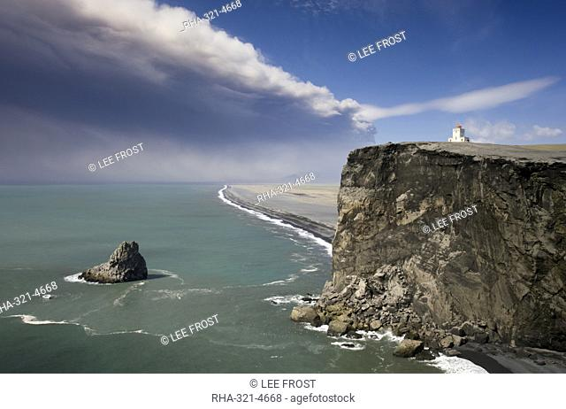 Headland with lighthouse at Dyrholaey looking towards a black volcanic sand beach stretching 15 miles into the distance and the ash plume of the...