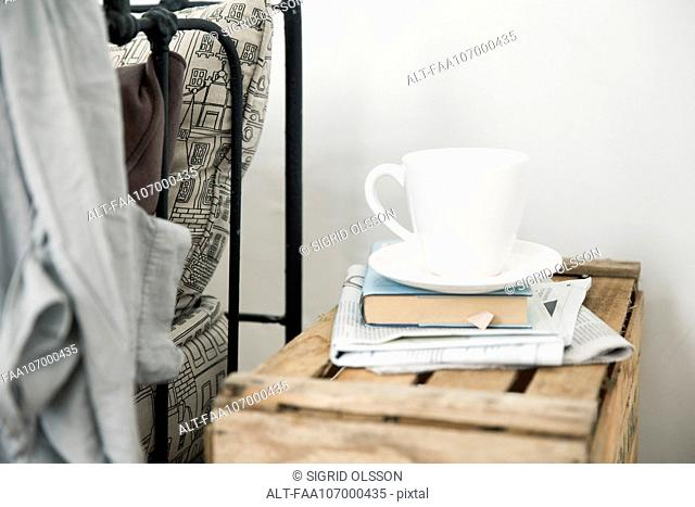 Coffee cup and book on night table