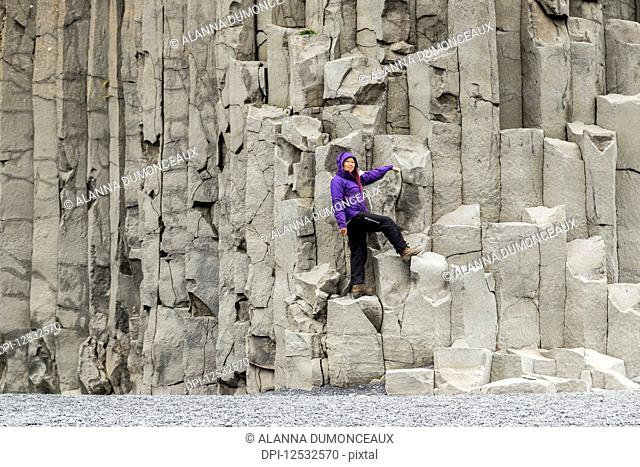 A female tourist poses on the basalt rock columns on the Reynisfjara beach in Southern Iceland; Iceland
