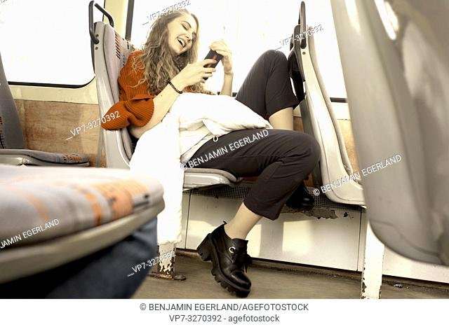 young woman sitting in public transport, using phone, happy laughing, in city Cottbus, Brandenburg, Germany