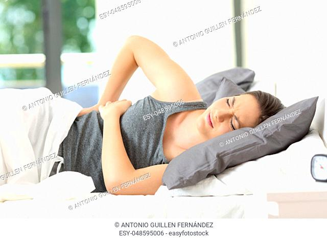 Woman lying on a bed waking up suffering back ache at home or hotel room