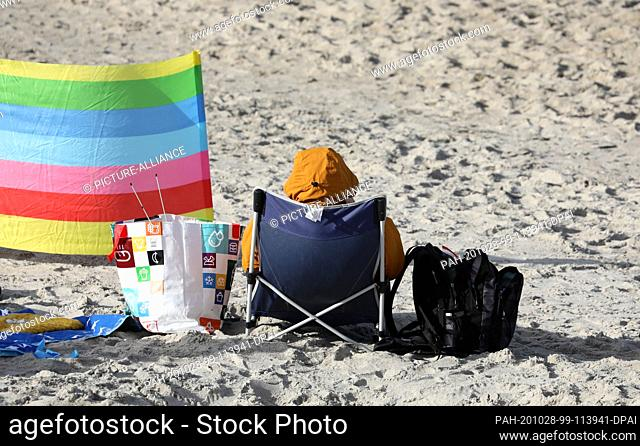 28 October 2020, Mecklenburg-Western Pomerania, Graal-Müritz: A beach visitor is sitting on a camping chair in the sand of the Baltic Sea