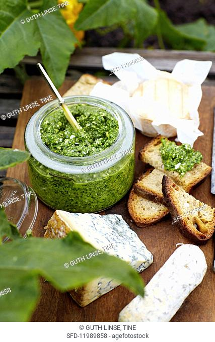 Pesto in a glass with bread and cheese