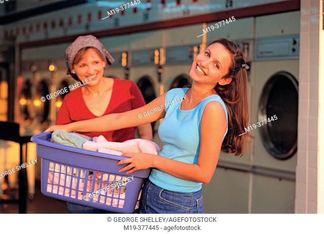 hispanic mother and daughter do laundry together