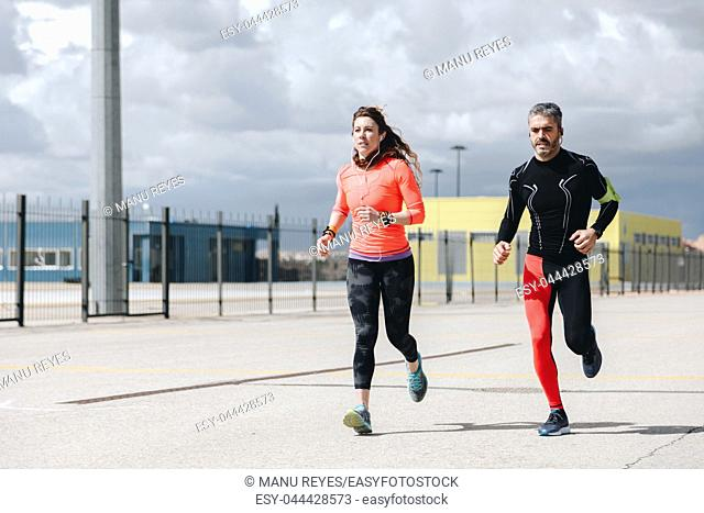 young adults couple running together in the street