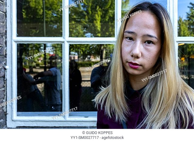 Tilburg, Netherlands. Portriat young Chinese woman in front of a window